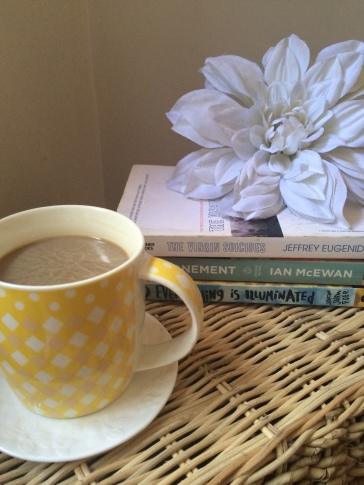 A cup of hazelnut coffee and a pile of next-in-line material