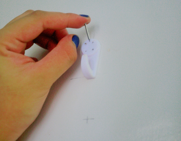 Finish off by hammering the center nail that comes with the hooks at an angle, to really anchor it on to the wall.