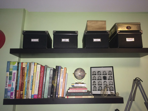 Boxes of supplies on the top shelf, decor books and some tchotchkes on the lower shelf